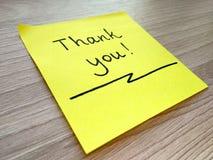 Dziękuje ciebie wiadomość na kleistej notatce na drewnianym tle fotografia royalty free