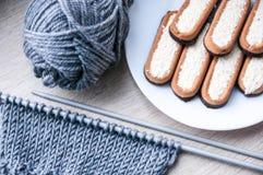 Dziać z popielatą wełną i ciastkami na bielu talerzu Fotografia Royalty Free
