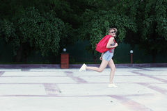 Działająca dziewczyna jest ubranym szkła, drelichowi skróty, szara koszula z plecakiem Fotografia Stock