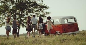 Działająca grupa przyjaciele w środku natura, ich retro autobus, dobrzy trybowi chłodzić i ono uśmiecha się 4K zbiory