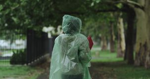 Działająca kobieta przez parc na deszczowym dniu, jest ubranym zieloną podeszczową kamizelkę 4k zdjęcie wideo