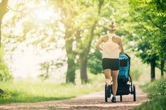 Działająca kobieta z wózkiem spacerowym cieszy się lato w parku fotografia stock
