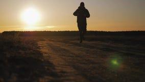 Działająca mężczyzna sylwetka w zmierzchu czasie Plenerowy przez cały kraj bieg Sportowy młody człowiek biega w naturze podczas zbiory