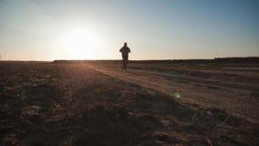 Działająca mężczyzna sylwetka w zmierzchu czasie Plenerowy przez cały kraj bieg Sportowy młody człowiek biega w naturze podczas zdjęcie wideo