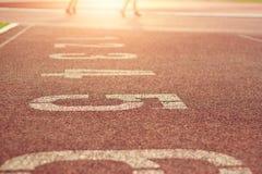 Działający ślad numerowy i rozmyte atletyka biega tło Zdjęcia Stock