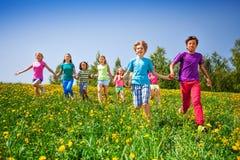 Działający dzieci trzyma ręki w zielonej łące Obraz Stock