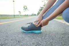 Działający uraz nogi wypadku sporta kobiety biegacza kaleczenie trzyma bolesną zwichniętą kostkę w bólu obraz stock