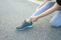 Działający uraz nogi wypadku sporta kobiety biegacza kaleczenie trzyma bolesną zwichniętą kostkę w bólu zdjęcie stock