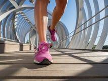 Działających butów zbliżenie żeński biegacz na nowożytnym moscie Fotografia Stock