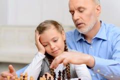 Dziad bawić się szachy z małą dziewczynką Fotografia Royalty Free