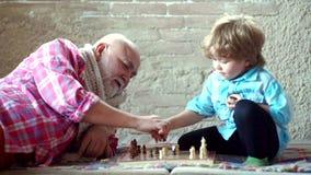 Dziad i wnuk jesteśmy bawić się szachowy i uśmiechnięty podczas gdy wydający czas wpólnie w domu bierka zdjęcie wideo