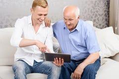 Dziad i wnuk używa pastylkę wpólnie Zdjęcia Stock