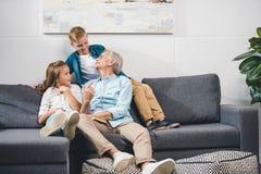Dziad i wnuki siedzi na kanapie obraz stock