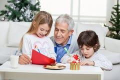 Dziad Pomaga dzieci W Writing listach Zdjęcie Royalty Free