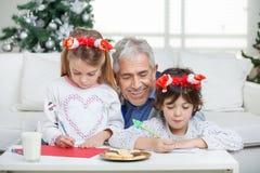 Dziad Pomaga dzieci W Writing listach Obraz Stock