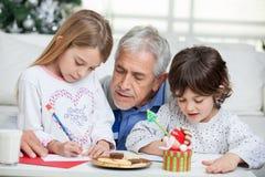 Dziad Pomaga dzieci W Writing listach Zdjęcie Stock