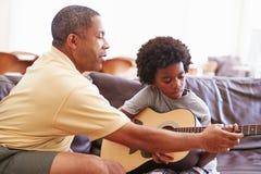 Dziadek nauczanie wnuk Bawić się gitarę Zdjęcie Royalty Free