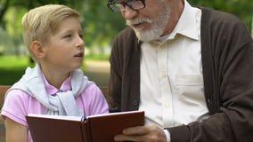 Dziadek nauczanie wnuka czytanie, odpoczywa na ławce w lato parku, rodzina zbiory