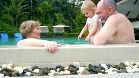 Dziadkowie i dziewczynka bawić się w pływackim basenie zbiory