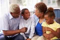 Dziadkowie i ich młodzi wnuki relaksuje w domu obraz royalty free