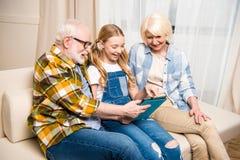 Dziadkowie, uśmiechnięty wnuczki obsiadanie na kanapie i używać cyfrową pastylkę obraz stock