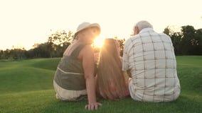 Dziadkowie z wnuczką siedzi outdoors, tylny widok zbiory