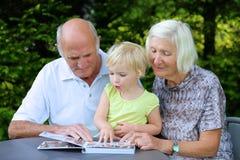 Dziadkowie z wnuka dopatrywania albumem fotograficznym zdjęcie royalty free