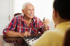 Dziadunio Bawić się Szachową grę planszowa Z wnukiem W Domu Obrazy Stock