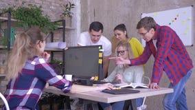 Dzień powszedni w ruchliwie kreatywnie biurze, coworkers stoi przy stołem z komputerem i dyskutuje biznesowych pomysły zbiory