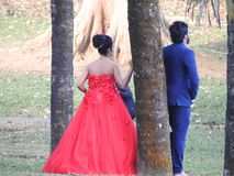 _ dzień zobowiązanie Państwo młodzi w ślubnej sukni, iść przez zielonej alei od plecy, Panna młoda w czerwieni zdjęcia royalty free
