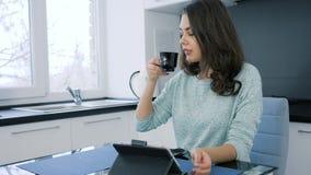 Dzień dobry pije kawę z pastylką na biurku, śliczna kobieta zdjęcie wideo