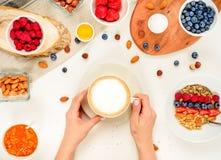 Dzień dobry - zdrowy śniadaniowy tło z oatmeal kawą, jagody, jajko, dokrętki Kawa, ręki, chwyt, filiżanka Biały drewniany karmowy zdjęcia stock