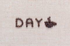 Dzień ikona pisać z kawowymi fasolami z filiżanką na bieliźnianej teksturze zamkniętej w górę zdjęcie royalty free