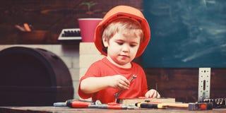 Dzieciństwa pojęcie Chłopiec sztuka jako budowniczy lub naprawiacz, praca z narzędziami Żartuje chłopiec w pomarańczowym ciężkim  zdjęcie royalty free