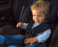 Dziecięca chłopiec ono uśmiecha się w samochodowym siedzeniu Obraz Stock