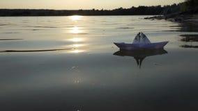 Dziecięca papierowa łódź pływa w jeziornej wodzie przy zmierzchem w mo zbiory wideo