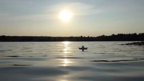 Dziecięca papierowa łódź unosi się w lasowym jeziorze przy zmierzchem w mo zbiory