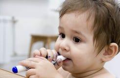 Dziecięcego dziecka dziecka berbecia siedzący rysunkowy obraz z kolorów ołówków kredkami na białym tle Zdjęcia Stock