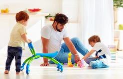 Dziecięcy berbecia dziecka odprowadzenie z iść fura podczas gdy ojciec i dzieciak bawić się gry wpólnie Zdjęcie Stock