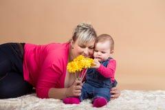 Dziecięcy dziecko z jego kolorem żółtym i mamą kwitnie Obraz Royalty Free