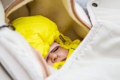 Dziecięcy sen w wózku spacerowym w zimy lasowym ciepło ubierającym żółty kombinezon obrazy stock