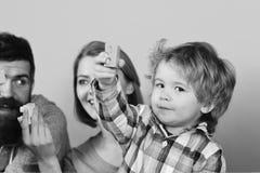 Dzieciństwo i bawić się pojęcie Mężczyzna z brodą, kobieta i chłopiec, bawić się na błękitnym tle Rodzina z ciekawymi twarzami wy Fotografia Stock