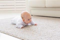 Dzieciństwo, niemowlęctwo i ludzie pojęć, - mała chłopiec lub dziewczyny czołganie na podłoga w domu obrazy stock