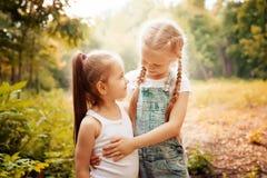 Dzieciństwo, rodzina, przyjaźń i ludzie pojęć, - dwa szczęśliwej dzieciak siostry ściska outdoors Fotografia Stock