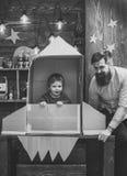 Dzieciństwo sen Chłopiec sztuka z tata, ojciec, mały kosmonauta siedzi w rakiecie robić z kartonu Dziecko śliczna chłopiec zdjęcie stock