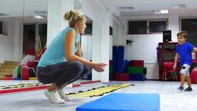 Dzieci ćwiczy salto pod nadzorem trenera zbiory wideo