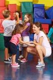 Dzieci ćwiczy z pepiniera nauczycielem w gym obraz stock