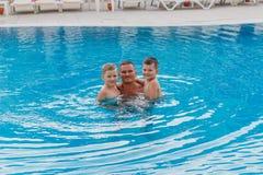 Dzieci ściska jego ojcują ` s szyję w błękitnym basenie obraz royalty free