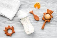 Dzieci akcesoria Drewniane zabawki, pacyfikator i butelka na popielatego drewnianego tła odgórnym widoku, fotografia stock