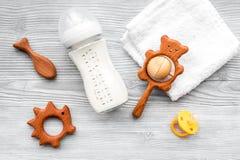 Dzieci akcesoria Drewniane zabawki, pacyfikator i butelka na popielatego drewnianego tła odgórnym widoku, zdjęcie stock